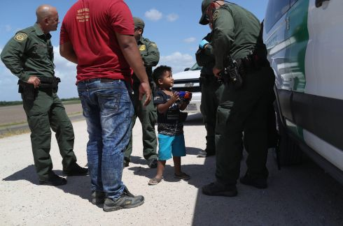 "A boy and father from Honduras are taken into custody by U.S. Border Patrol agents near the U.S.-Mexico Border on June 12, 2018 near Mission, Texas. The asylum seekers were then sent to a U.S. Customs and Border Protection (CBP) processing center for possible separation. U.S. border authorities are executing the Trump administration's ""zero tolerance"" policy towards undocumented immigrants. U.S. Attorney General Jeff Sessions also said that domestic and gang violence in immigrants' country of origin would no longer qualify them for political asylum status.  (Photo by John Moore/Getty Images)"