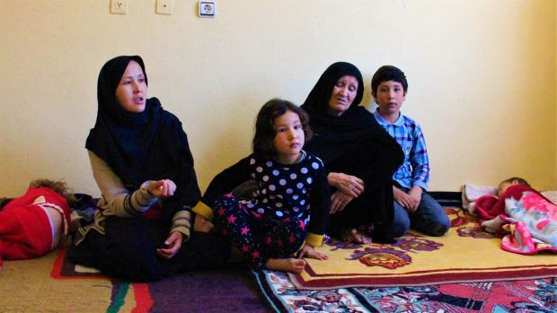 Hakima (left), her mother-in-law Hawa, and children in their bare apartment in Van, Turkey