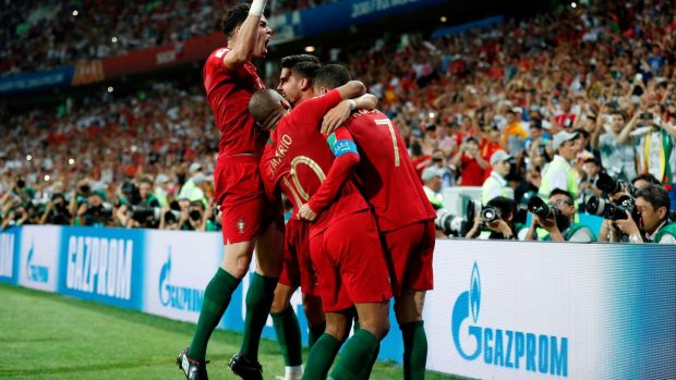 Cristiano Ronaldo is mobbed by his Portuguese team-mates after completing his hat-trick against Spain in Sochi. Photograph: Adrian Dennis/AFP/Getty Images