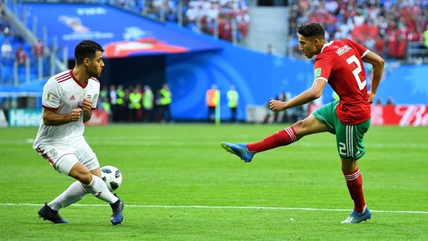Morocco's Achraf Hakimi has a shot at goal as Iran's Morteza Pouraliganji attempts to block during the World Cup game in St Petersburg. Photograph: Dylan Martinez/Reuters