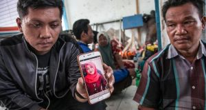 A man shows a smartphone photo of his daughter Ayu Safitri, one of the passengers missing after a boat capsized on June 18th. Photograph: Ivan Daman/ AFP/Getty Images