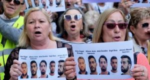 People shout slogans while holding signs during a protest outside the City of Justice in Valencia, Spain in April. Photograph: Heino Kalis/Retuers