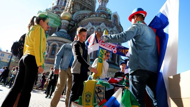 A street vendor sells flags and scarfs in front of St Isaac's Cathedral near the Fan Fest area in St Petersburg. Photograph: EPA