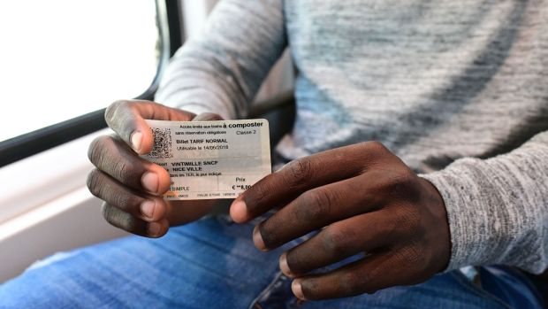 A migrant shows his train ticket as he attempts to cross the border from Ventimiglia in Italy to Menton in France. Photograph: Miguel Medina/AFP/Getty I