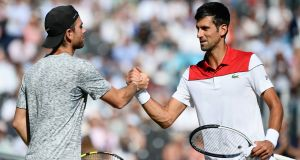 France's Adrian Mannarino  and Serbia's Novak Djokovic shake hands after the quarter-final match   at Queen's Club Friday in London. Photograph: Patrik Lundin/Getty Images for LTA