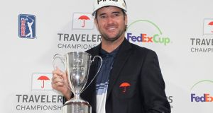 Bubba Watson poses for photos with the trophy after winning the Travelers Championship on the PGA Tour. Photo: Stew Milne/AP Photo