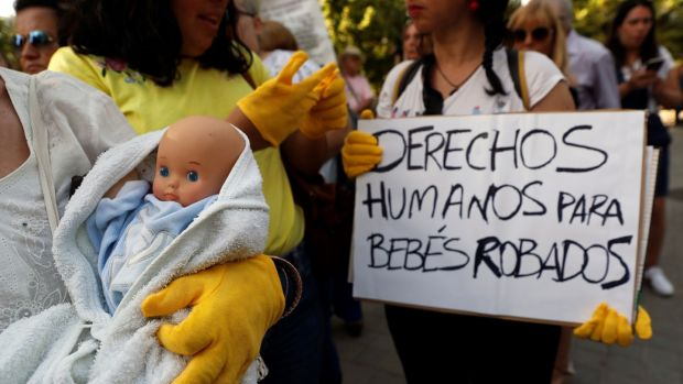 "A protester holds a placard reading, ""Humans rights for stolen babies"" outside the Madrid court on Tuesday where a doctor went on trial on charges of child abduction and falsification of documents. Photograph: Chema Moya/EPA"