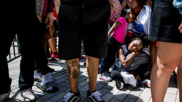 Rico Hendrix (19) sits alongside his sisters SaRiah (8) and Ceecy (3) at the front of the line of fans at a memorial and viewing for rapper XXXTentacion. Photograph: Scott McIntyre/The New York Times