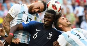 France's midfielder Paul Pogba heads the ball with Argentina defenders Nicolas Otamendi  and  Nicolas Tagliafico during the  World Cup round of 16 match at the Kazan Arena. Photograph: Franck Fife/AFP/Getty Images