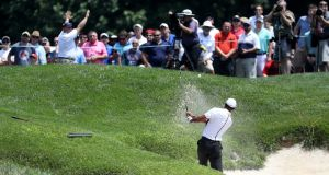 Tiger Woods hits out of a bunker on to the second green during the third round of the Quicken Loans National at TPC Potomac in Maryland. Photograph: Rob Carr/Getty Images