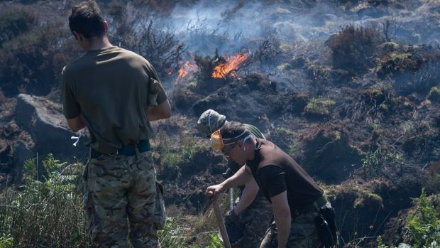 A British Ministry of Defence (MOD) handout photograph shows British Army soldiers of 4 Scots help dig ditches and 'breaks' to maintain the fires as they continue to support Great Manchester Fire and Rescue Service with the Saddleworth Moor fire, north west England, Britain, 29 June 2018. Photograph: Sgt Donald Todd via EPA.