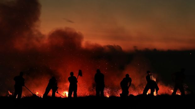 Firefighters tackle a wildfire on Winter Hill near Bolton. Photograph: Danny Lawson/PA Wire.