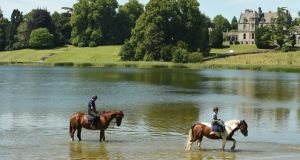 Peter and Turlough McDonnell riding their horses thorugh the lake in front of Castle Leslie
