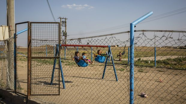 Youths play on swings at Roj Camp for the families of Islamic State members in Kurdish-controlled northern Syria. Photograph: Ivor Prickett/The New York Times