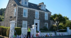 A police officer guard as a search takes place at a house on Ardbeg Road on the Isle of Bute in Scotland. Photograph: John Linton/PA Wire