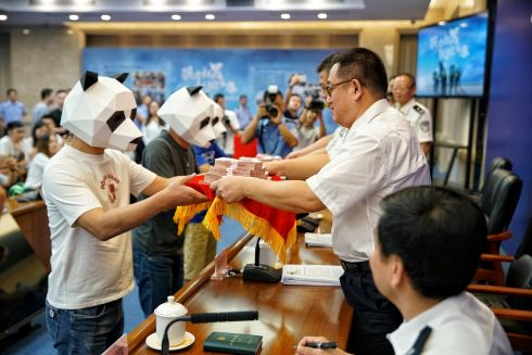 PANDA POLICE: Whistleblowers wearing panda masks receive cash awards for reporting gang crimes from police officers at a news conference in Guangzhou, Guangdong province, China. Photograph: Reuters
