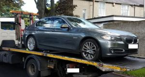 A file photograph of a stolen BMW being recovered by gardaí. Many criminals involved in organised crime are now opting to drive less ostentatious vehicles.  Photograph: Garda Síochána