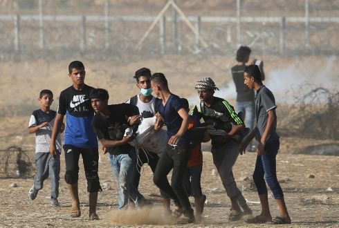 ISRAEL-PALESTINE CONFLICT: A wounded Palestinian is evacuated during a protest in the southern Gaza Strip. Photograph: Ibraheem Abu Mustafa/Reuters