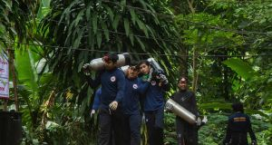 Thai rescue personnel carry oxygen cylinders back to their base camp at the entrance to the cave where members of a youth soccer team is currently trapped. Photograph: Lauren DeCicca/Getty Images