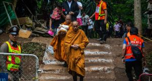 Monks lead out the family members of the boys from the cave site after a morning prayer on Saturday. Photograph: Lauren DeCicca/Getty Images