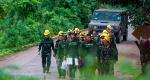 Thai soldiers walk out from the Tham Luang cave area as operations continue for the 8 boys and their coach trapped at the cave. Photograph: Ye Aung Thyue/AFP/Getty Images