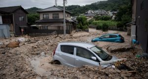Cars trapped in the mud after floods in Saka, Hiroshima prefecture. Photograph: AFP