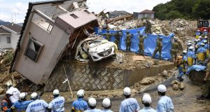 Rescue workers look for missing people in a house damaged by heavy rain in Kumano town, Hiroshima Prefecture, on Monday. Photograph: Reuters