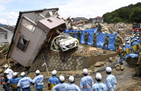 FLOODING AFTERMATH: Rescue workers look for people missing from a house which was uprooted by floods caused by heavy rains, in Kumano town, Hiroshima Prefecture, Japan. Photograph: Kyodo/Reuters