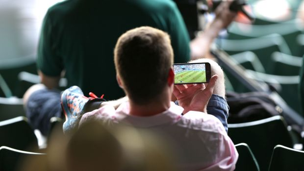 A tennis fan watches England's World Cup quarter-final win over Sweden while at Wimbledon. Photograph: Steven paston/PA