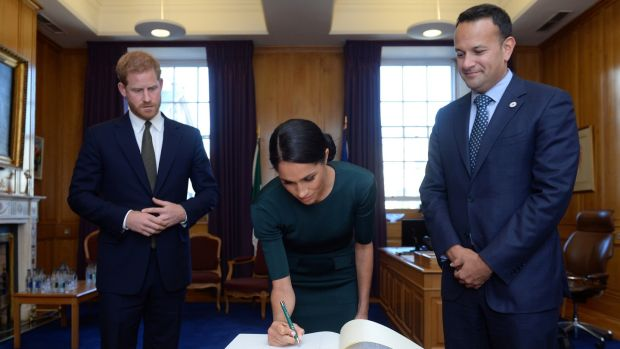The Taoiseach looks on as the Duke and Duchess of Sussex sign the visitors' book at Government Buildings on Tuesday. Photograph: Clodagh Kilcoyne/Pool/AFP/Getty Images.