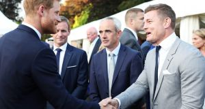 Prince Harry, the Duke of Sussex, meets  Brian O'Driscoll and  Ruby Walsh at a garden party in the British ambassador's Dublin residence. Photograph: Julien Behal Photography.