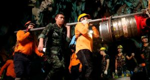 Rescue workers remove equipment from the cave. Photograph: Soe Zeya Tun/Reuters
