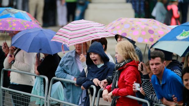 A group waiting for Meghan Markle and Prince Harry in Trinity College Dublin during an unusual rain shower. Photograph: Nick Bradshaw /Pool/The Irish Times