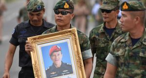 An honour guard holding up a picture of Samarn Kunan (38), a former member of Thailand's elite Navy Seal unit, who died during a rescue operation to save 12 boys and their soccer coach trapped inside a flooded cave. Photograph: Panumas Sanguanwong/Reuters