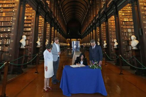 TRINITY COLLEGE: Meghan signs the visitors' book. Photograph: Getty Images