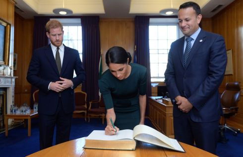 GOVERNMENT BUILDINGS: Meghan signs the visitors' book.  Photograph: Clodagh Kilcoyne/EPA