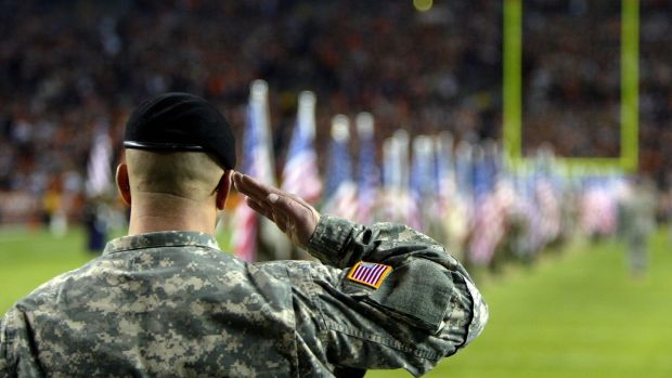 A member of the US Armed Forces salutes during pregame ceremonies beforeNew England Patriots' meeting with the Denver Broncos. Photo: Doug Pensinger/Getty Images