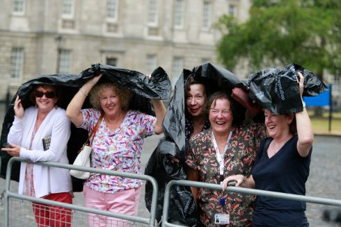 Waiting in Trinity College - as the rain makes an appearence - for Meghan Markle and Prince Harry. Photograph: Nick Bradshaw/Pool/The Irish Times