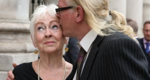 Tressa Donnelly Reeves receives a kiss from her son, Paddy Farrell (also known as André Donnelly),  at the Four Courts on Thursday after the announcement of a settlement of their High Court action. Photograph: Collins Courts