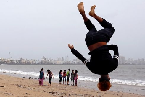 Beachgoers walk on by as a boy somersaults on a beach in Mumbai, India. Photograph: Danish Siddiqui/Reuters