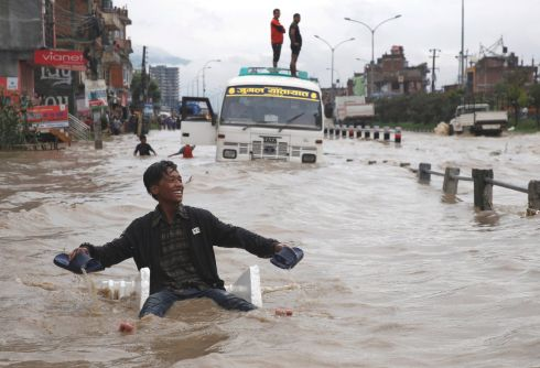 An improvised raft is deployed to manoeuvre through floodwater after incessant rainfall in Bhaktapur, Nepal. Photograph: Navesh Chitrakar