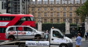 "Bashed car with a banner reading ""For sale – but no one's buying May's Brexit banger"" is driven around Parliament Square in London. Photograph: Chris J Ratcliffe/Getty Images"