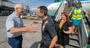 Ennis-based diver Jim Warny is greeted by his dad, Rene Warny, after he landed in Shannon Airport. Photograph: Arthur Ellis.