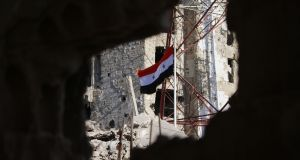 The Syrian national flag rises in the midst of damaged buildings in Daraa-al-Balad, an opposition-held part of the southern city of Daraa, on Thursday. Photograph: Mohamad Abazeed/AFP/Getty Images