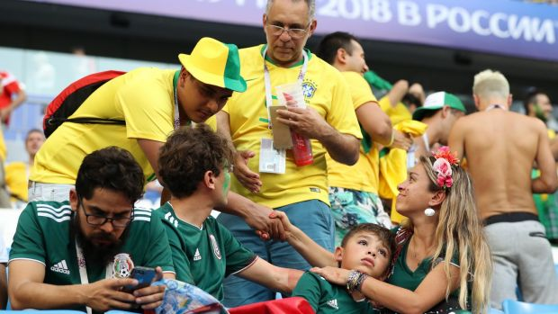 Brazil fans console Mexico fans after their 2-0 last-16 victory in Samara. Photograph: Ryan Pierse/Getty