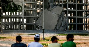 Palestinian youths look at a building that was damaged by an Israeli air strike in Gaza City on July 14, 2018. Photograph: AFP/Getty Images
