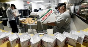 An employee fills boxes of doughnut   at a Krispy Kreme store in  Maine, US. Photograph:   Shawn Patrick Ouellette/Portland Press Herald via Getty Images