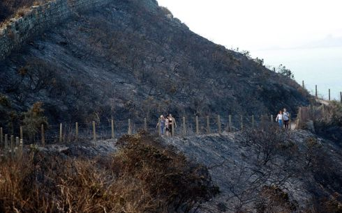 BURNED AND BLACKENED: Walkers enjoy the recently reopened Bray Head cliff walk to Greystones, on the Co Wicklow coast, after serious gorse fires recently had prompted its closure. Photograph: Nick Bradshaw/The Irish Times