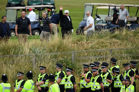 TO SCOTLAND FOR GOLF: US president Donald Trump waves from behind police lines while playing golf at Trump Turnberry Luxury Collection Resort during his first official visit to the United Kingdom, in Turnberry, Scotland. Photograph: Leon Neal/Getty Images