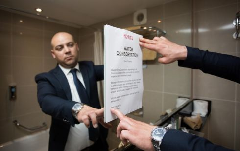 FEELING THE DROUGHT: Zoran Varmuza, duty manager at the Academy Plaza Hotel, O'Connell Street, Dublin, erects a sign in a restroom asking guests to conserve water as water shortages are felt. Photograph: Tom Honan/The Irish Times